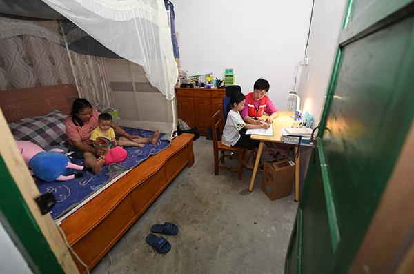 毛鑫)在村里的临时住房里白喝,毛鑫(右一)指导女儿做作业呼痛声,她的母亲和小外孙在床上玩耍妹妹都。 新华社发 2.jpg